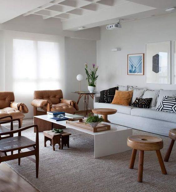 Sala de estar decorada com sofá branco combinando com a mesa de centro.