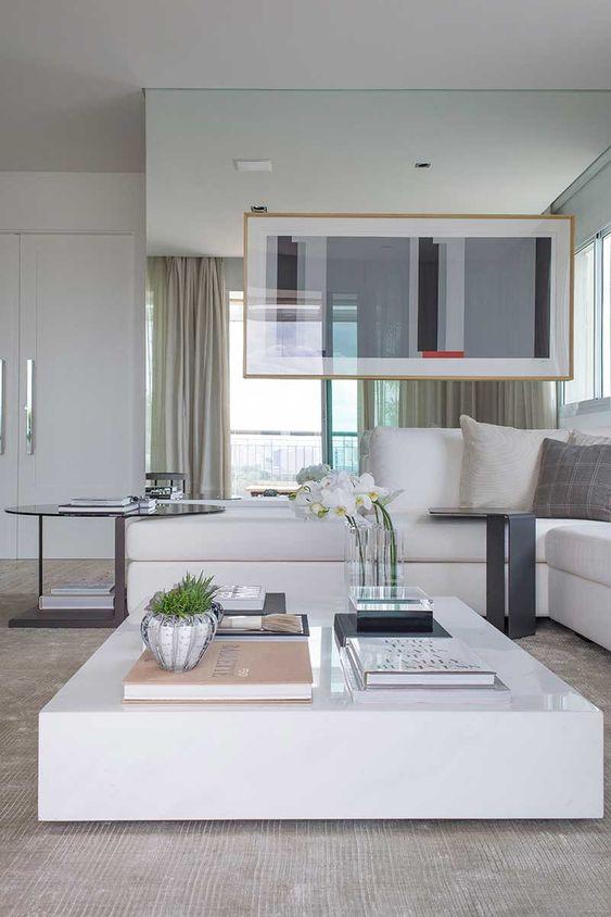 Sala de estar decorada com mesa de centro simples e branca.