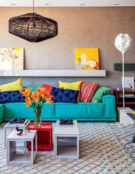 Sala de estar decorada com sofá e almofadas coloridas e mesa de centro.