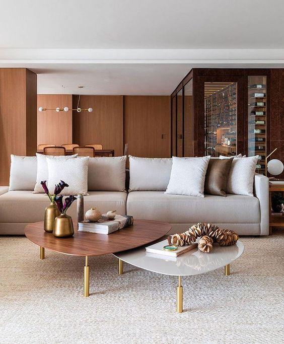 Sala de estar decorada em branco e marrom com mesa de centro dupla.