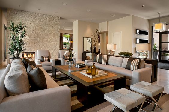 Grande sala com tapete e almofadas listradas.