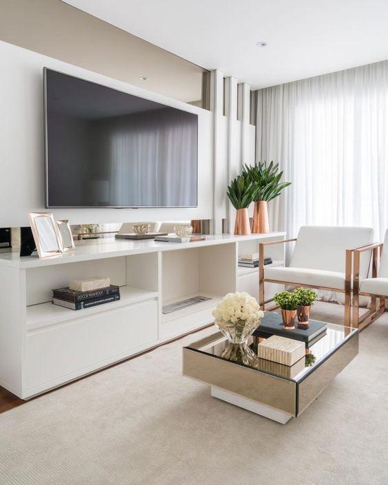 Sala de estar decorada com mesa de centro espelhada e vasos de planta e flores.