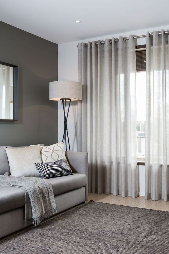 Sala de estar decorada em branco e cinza com cortina, almofadas e abajur.