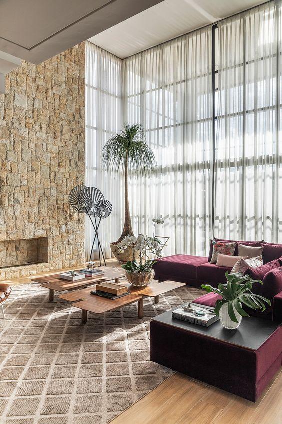 Sala de estar decorada com lareira, sofá vinho e cortina branca em parede de janelas.