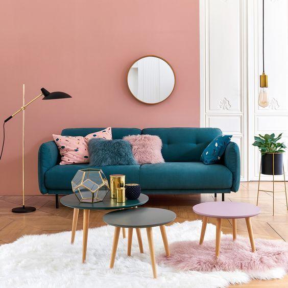 Sala de estar decorada na cor rosa com sofá azul.