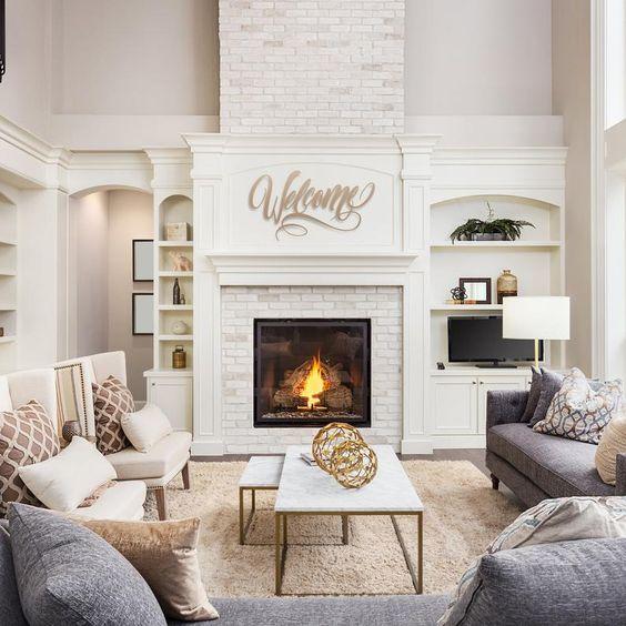 Sala de estar decorada com sofás cinzas, poltronas brancas e lareira.