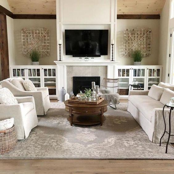 Sala de estar decorada com artigos na parede, mesa de centro, tapete e lareira.