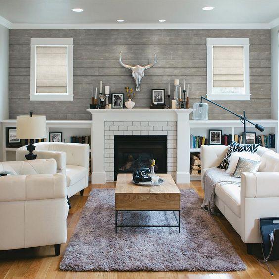 Sala de estar decorada em branco e cinza com lareira e suportes para livros.