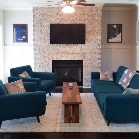 Sala de estar decorada com móveis azuis e lareira.