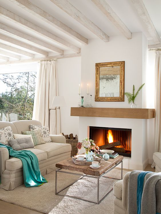 Sala de estar decorada com cores neutras, lareira e mesa de centro rústica.