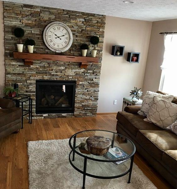 Sala de estar decorada com lareira em parede de pedra.