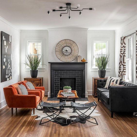 Sala de estar decorada em branco e preto com poltronas laranjas.