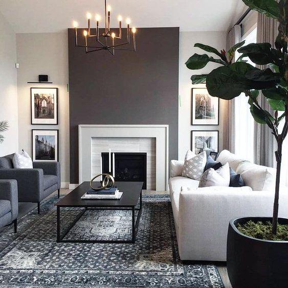 Sala de estar decorada em branco e cinzo com lareira e quadros.