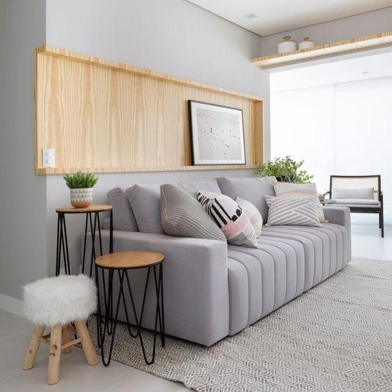 Sala decorada com sofá cinza claro com almofadas.