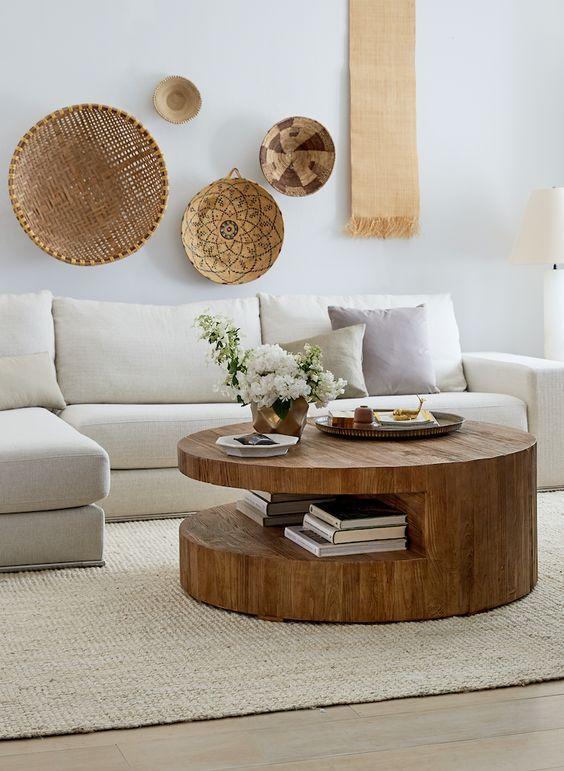 Sala de estar decorada branca e marrom com livros na mesa de centro.
