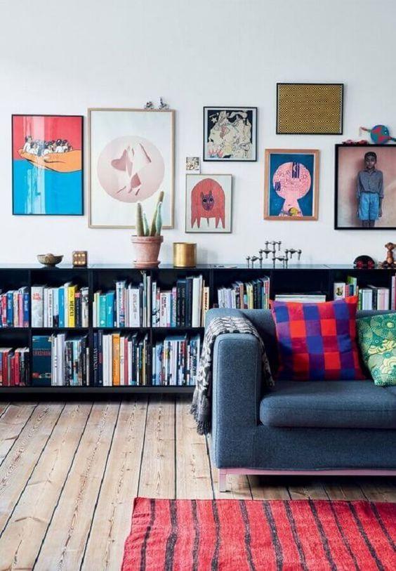 Sala de estar decorada com quadros, almofadas e livros.