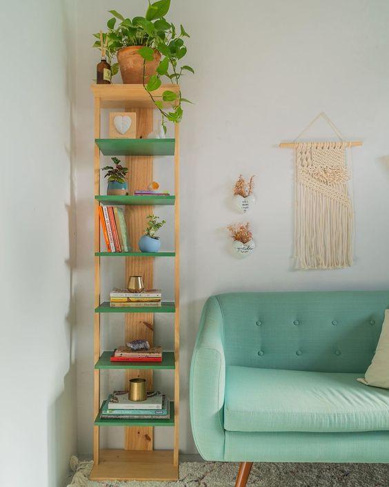 Suporte de madeira com prateleiras verdes para livros e artigos decorativos.