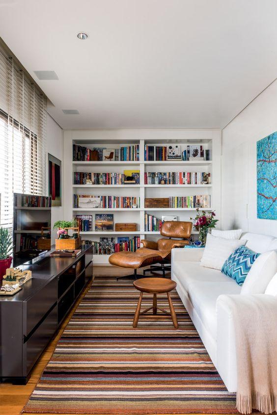 Sala de estar decorada em branco, azul e marrom com nichos embutidos na parede.