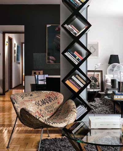 Sala de estar decorada com poltrona, mesa de centro e nichos para livros.