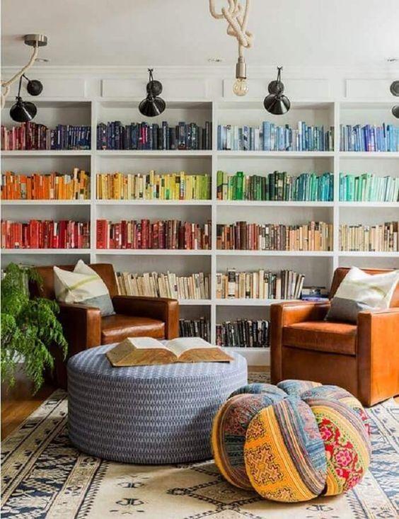 Livros organizados por cor em móvel branco.