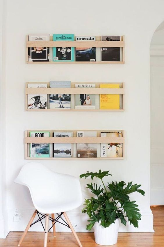 Sala de estar decorada branca com prateleiras para livros.