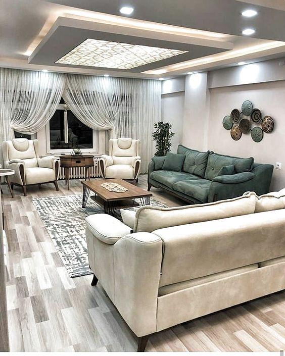 Sala de estar com cores neutras e um sofá em verde escuro.