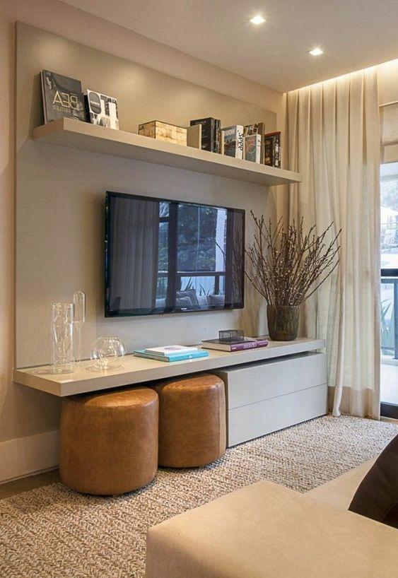 Painel de tv simples de cor neutra com prateleira para livros.