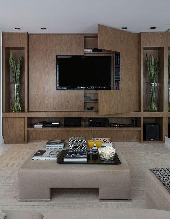 Sala de estar decorada com painel que é um armário de madeira.