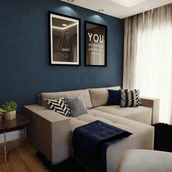Parede azul marinho, sofá bege e quadros em preto e branco.