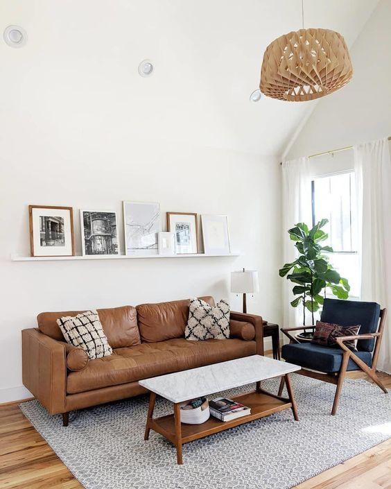 Sofá marrom e quadros brancos com moldura combinando com o sofá.