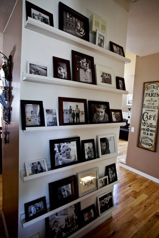 Sala de estar decorada com prateleiras para fotos.