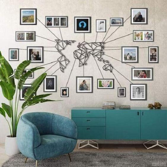 Poltrona e armário azuis e escultura do mapa mundi com fotos na parede.