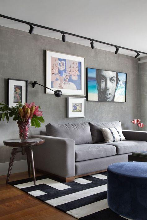 Sala de estar com iluminação direcionada aos quadros.