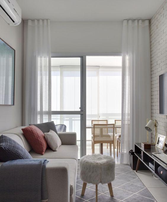 Sala de estar pequena com tapete branco e cinza.