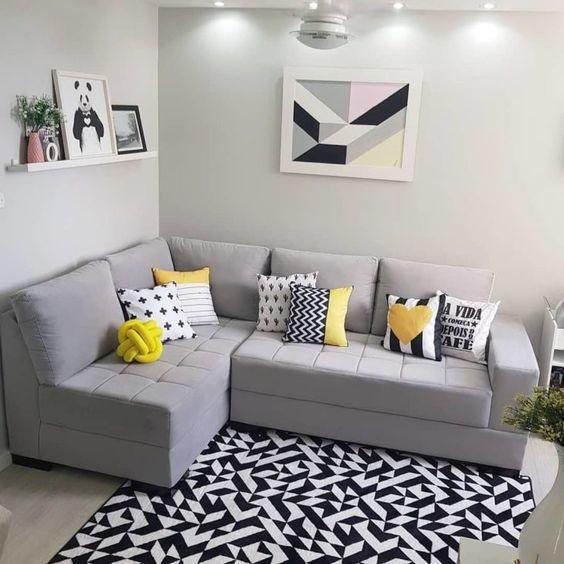 """Sala  decorada com sofá em """"L"""" e almofadas chamativas."""