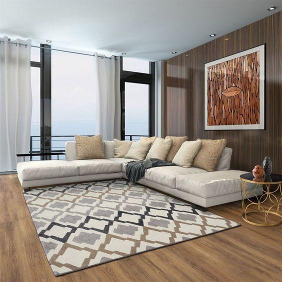 Parede e chão amadeirados e decorada com quadro, mesinha, tapete e almofadas.