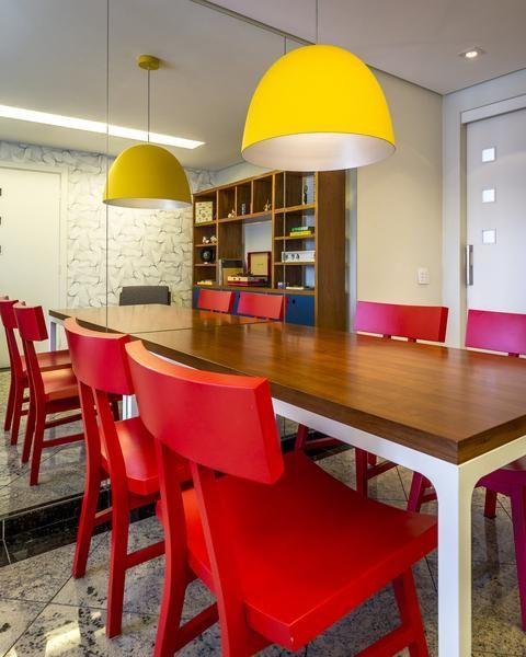 pendentes amarelos e cadeiras vermelhas em sala de jantar