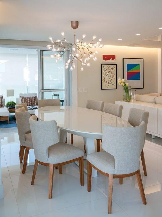 mesa oval com cadeiras estofadas brancas