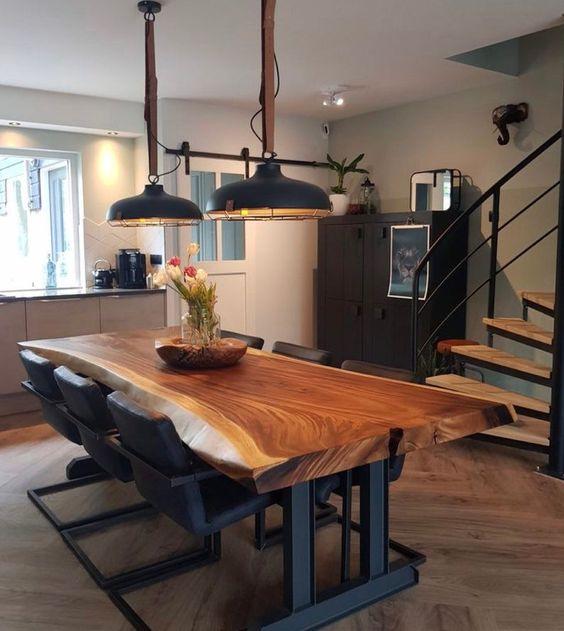 Sala de jantar decorada com cadeiras, lustres e pés da mesa pretas.