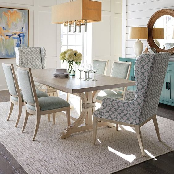 Sala de jantar simples com poltronas nos cantos da mesa.
