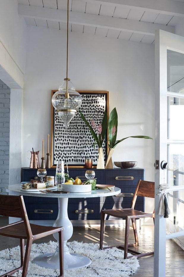 Sala de jantar decorada com armário azul, quadro preto e branco, plantas e vasos.