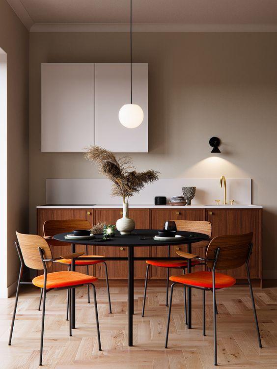 Sala de jantar com cadeira de madeira e assentos laranja.