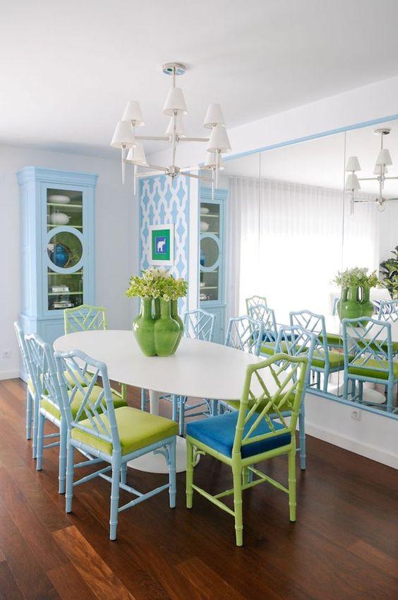 Parede espelhada em sala de jantar com mesa oval e cadeiras coloridas.