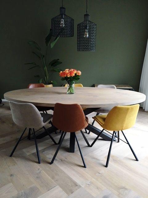 Sala de jantar com parede verde e lustres pretos de diferentes tamanhos.
