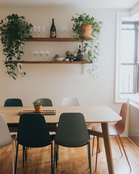 Sala de jantar com cadeiras coloridas e prateleiras com taças, louças, plantas e bebidas.