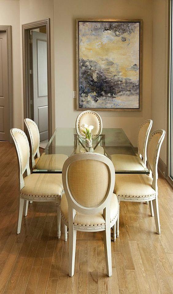 Sala de jantar decorada com mesa de vidro e cadeiras cor creme e branco.