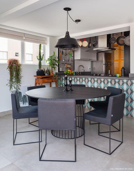 Sala de jantar com mesa redonda e cadeiras pretas modernas.
