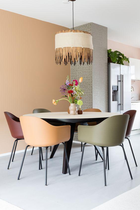 Sala de jantar simples com cadeiras coloridas.
