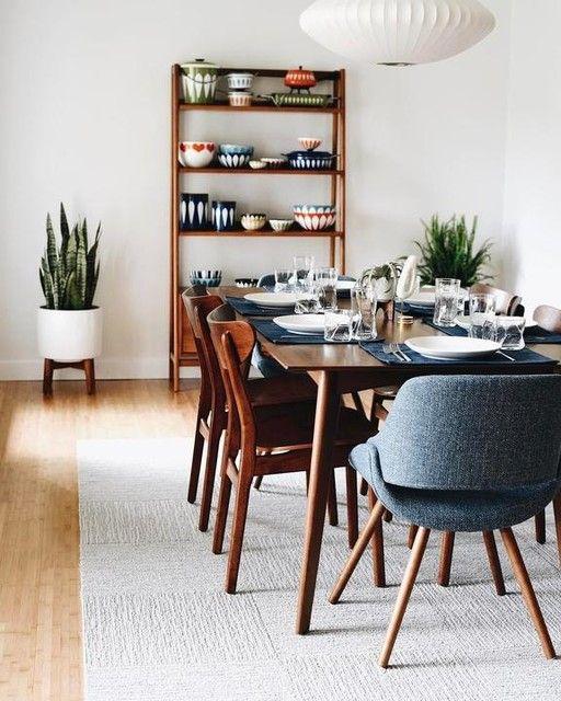 Sala de jantar com móvel de prateleiras com louças expostas.