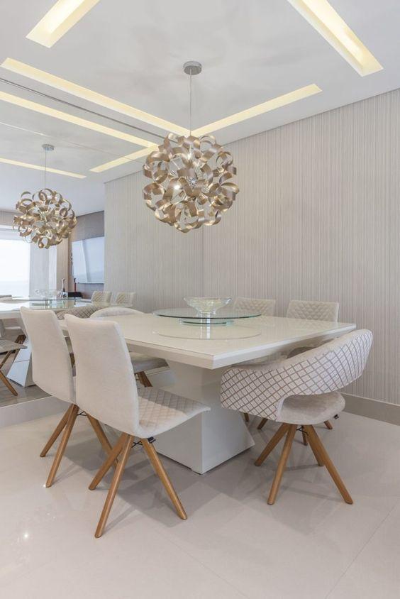 Mesa de jantar quadrada com dois modelos de cadeiras em cômodo de cores neutras.